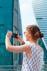 Girl making photo of business center in downtown
