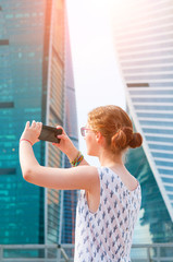 Young girl taking a picture of skyscrapers with smartphone