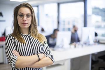 Giovane manager con camicia a righe bianche e nere e braccia conserte guarda seria di fronte a se , sfondo ufficio con colleghi