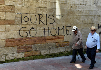 People walk past a graffiti in the historic center of Oviedo