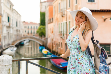 Young woman talking on a cell phone whilst stood on a bridge in Venice.