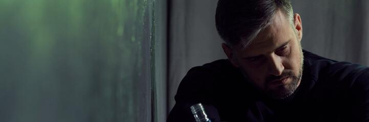 Man in despair holding bottle