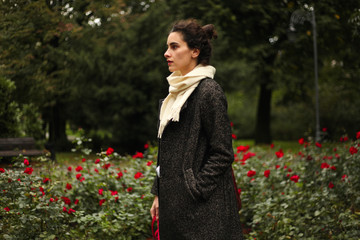 Portrait of a stylish young woman standing in a park, red roses behind her