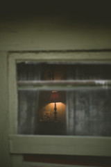 A lamp glows through the shabby window frame of an old house