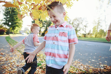 Young brothers having fun together outside in yellow leaves