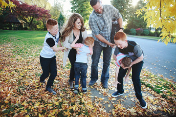 Young family having fun together in fall with yellow leaves
