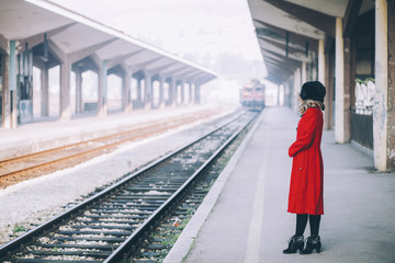 Young beautiful woman curly hair in a red coat and russian fur hat on a train station