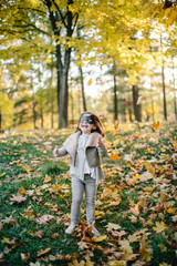 Little girl with a face mask is playing in autumn park and throw autumn leaves