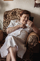 Old woman using smartphone (tablet) sitting in chair smiling