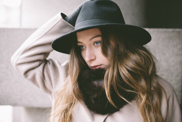 portrait of young woman with hat on the street