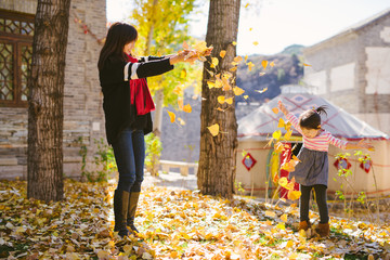 Young mother playing with her toddler daughter in autumn park