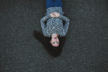 Young black haired woman lying down on sidewalk