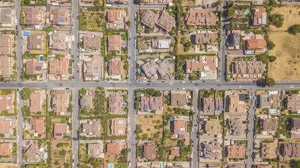 Vista aerea ortogonale di una parte del quartiere Marco Simone nella periferia nord a Roma. Tra le strade strette, le ville e i palazzi si vedono alberi. Sugli edifici ci sono antenne e parabole.