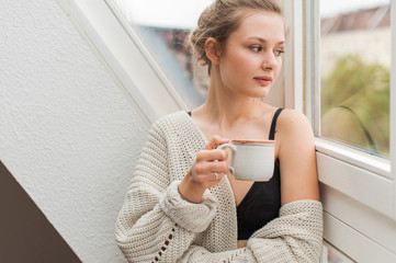 Young Woman in Her Pajamas Sitting in a Window Drinking out of a Mug