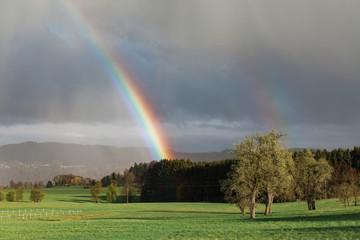 Colorful rainbow arcing through stormy air