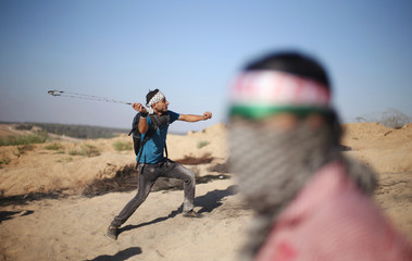 Palestinian protester uses a sling shot to hurl stones at Israeli troops during clashes near the border between Israel and Central Gaza Strip