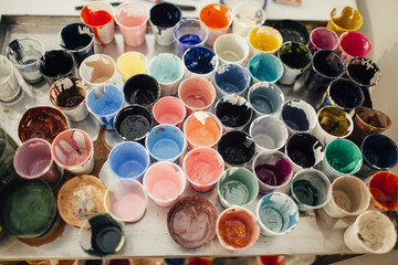 High angle view of messy watercolor paint glasses