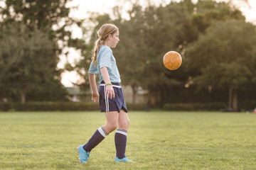 Side view of girl playing soccer on field