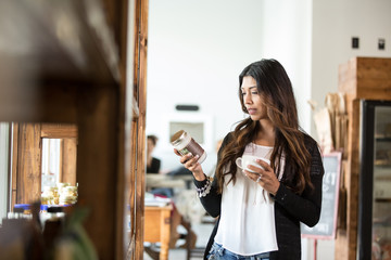 Woman reading label on jar while holding coffee cup in cafeteria