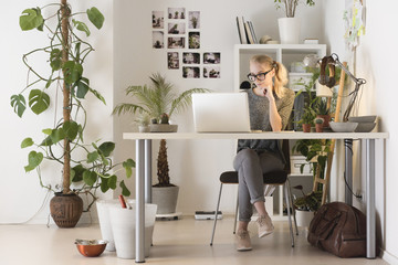 Full length of creative businesswoman using laptop in office