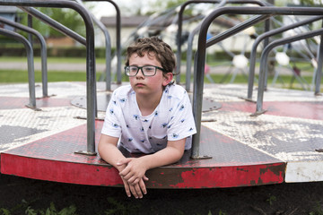 Thoughtful boy lying on merry-go-round at playground