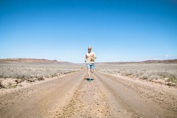 Full length of man running on dirt road against clear blue sky