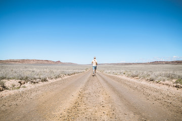 Rear view of man running on dirt road against clear blue sky