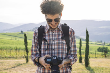 Happy young man watching pictures on digital camera while standing against hills