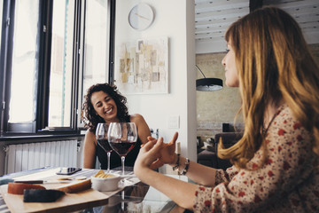 Cheerful female friends talking while sitting at restaurant table