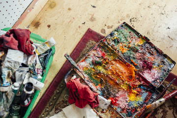 High angle view of colorful messy palette on table at workshop