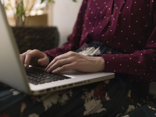 Midsection of woman using laptop computer at home