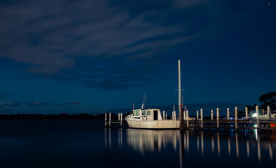 White Boat tied to a Pier at Night