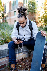 Male African American college student listening to music on campus