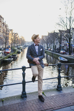 Young man with ukelele standing on a bridge dressed in a classic suit