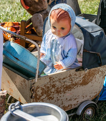 display of retro baby carriage and doll at garage sale