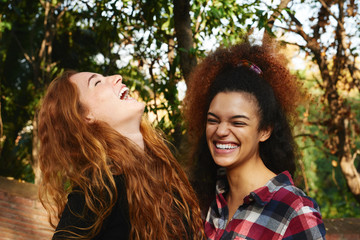 two young girlfriends laughing while hugging