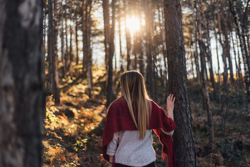 Back portrait of blond woman in the forest
