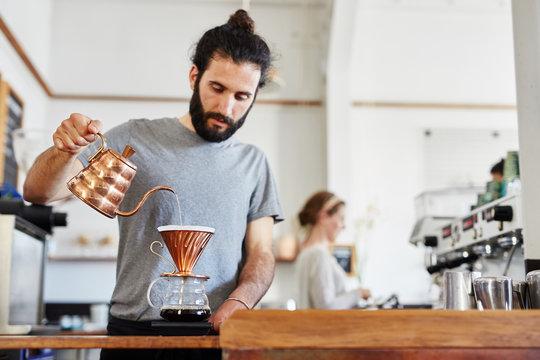Bearded barista making coffee through chemex