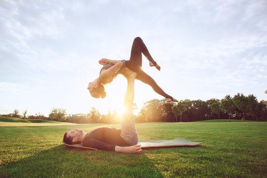People practice acro yoga outdoors healthy lifestyle