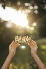 Woman's hands holding gold tiara