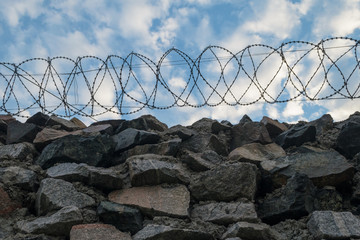 A wall of grey stone topped with barbed wire.