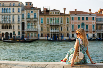 girl sitting on a pier near the canal at the venice. Italy