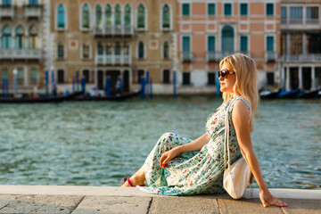 Girl female traveler sitting in Venice at sunrise and enjoy the area without people. The main square of the old town. Italy.