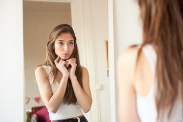 Portrait of young woman looking in the mirror