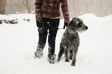 young woman holding her dog in the snow