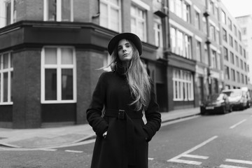 Young elegant woman in the street with hat and coat
