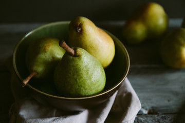 Pears in a bowl. Dark light.