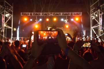 Person taking a picture with your smartphone at a concert in the evening