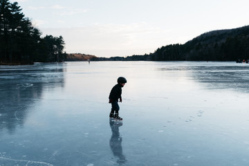 little kid skating on a lake