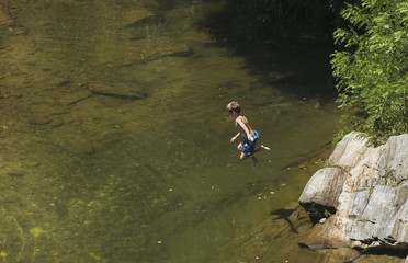Playful boy jumping in river.